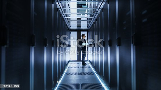 899720520istockphoto Male IT Engineer Works on a Laptop at the end of a Corridor in a Big Data Center. Rows of Rack Servers are Seen. 802302158