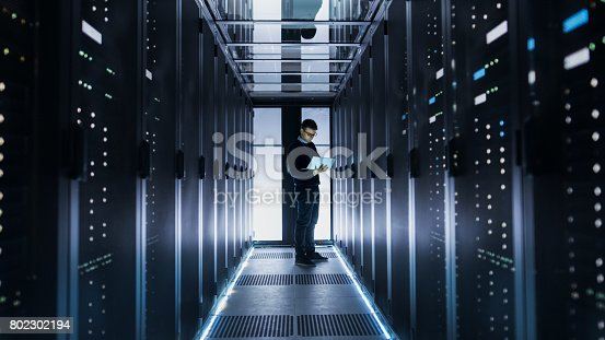 802303672istockphoto Male IT Engineer Works on a Laptop at the end of a Corridor in a Big Data Center. Rows of Rack Servers are Seen. 802302194