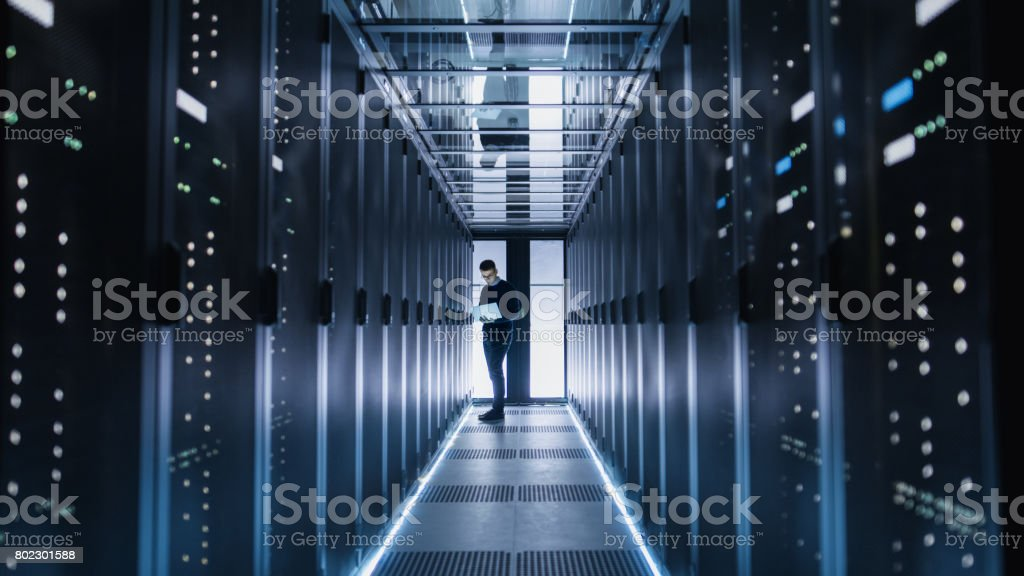 Male IT Engineer Works on a Laptop in a Big Data Center. Rows of Rack Servers are Seen. stock photo