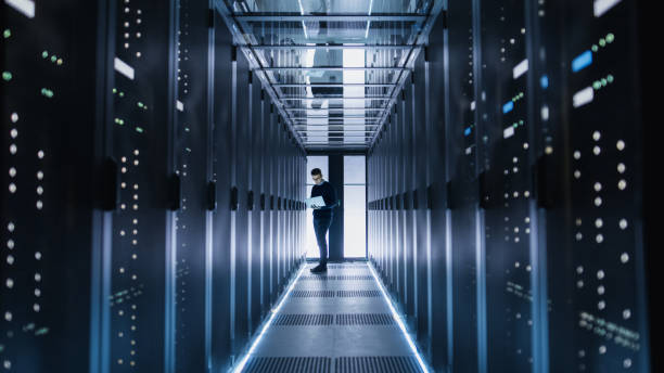 male it engineer works on a laptop in a big data center. rows of rack servers are seen. - network server stock pictures, royalty-free photos & images