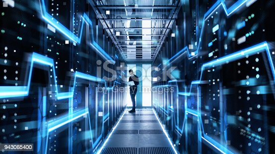 802303672istockphoto Male IT Engineer Works on a Laptop in a Big Data Center. Rows of Rack Servers with High Speed Internet Visualization. 943065400