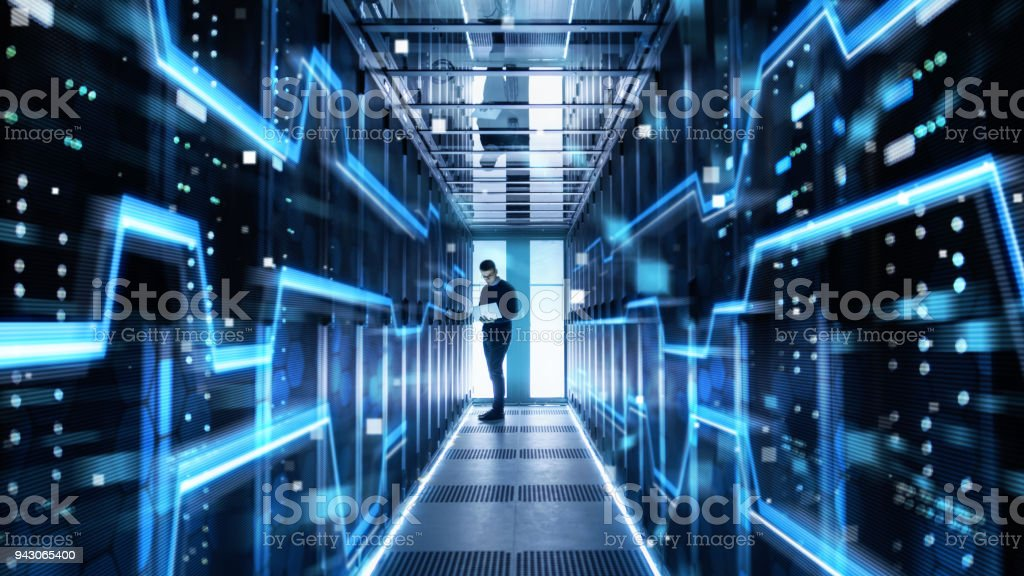 Male IT Engineer Works on a Laptop in a Big Data Center. Rows of Rack Servers with High Speed Internet Visualization. stock photo