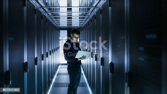 802303672istockphoto Male IT Engineer Works on a Laptop in front of Server Cabinet at a Big Data Center. Rows of Rack Servers are Seen. 802302950
