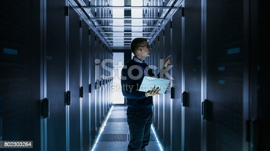 802303638istockphoto Male IT Engineer Works on a Laptop in front of Server Cabinet at a Big Data Center. Rows of Rack Servers are Seen. 802303264