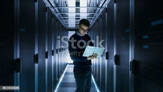 899720520istockphoto Male IT Engineer Works on a Laptop in front of Server Cabinet at a Big Data Center. Rows of Rack Servers are Seen. 802303636