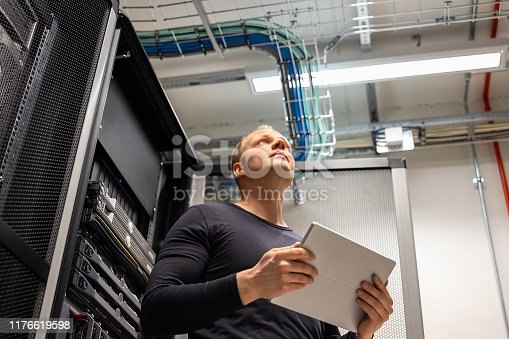 istock Male IT Professional Holding Digital Tablet Planning Changes in Datacenter 1176619598