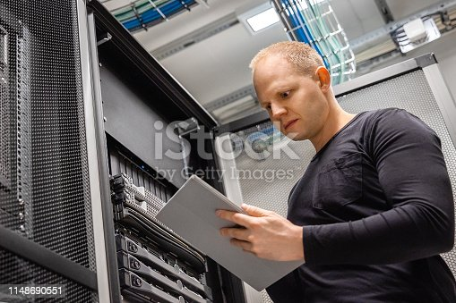istock Male IT Professional Using Digital Tablet to Monitor Datacenter Status 1148690551