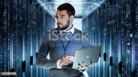 istock Male IT Server Technician Specialist Holds Laptop and Looking on Raining Script Code in Rack Sever Cabinet. He is Standing in Data Center. 943065398