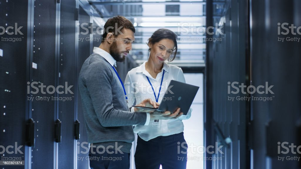 Male IT Specialist Holds Laptop and Discusses Work with Female Server Technician. They're Standing in Data Center, Rack Server Cabinet is Open. Male IT Specialist Holds Laptop and Discusses Work with Female Server Technician. They're Standing in Data Center, Rack Server Cabinet is Open. Administrator Stock Photo