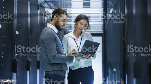 Male It Specialist Holds Laptop And Discusses Work With Female Server Technician Theyre Standing In Data Center Rack Server Cabinet Is Open Stock Photo - Download Image Now