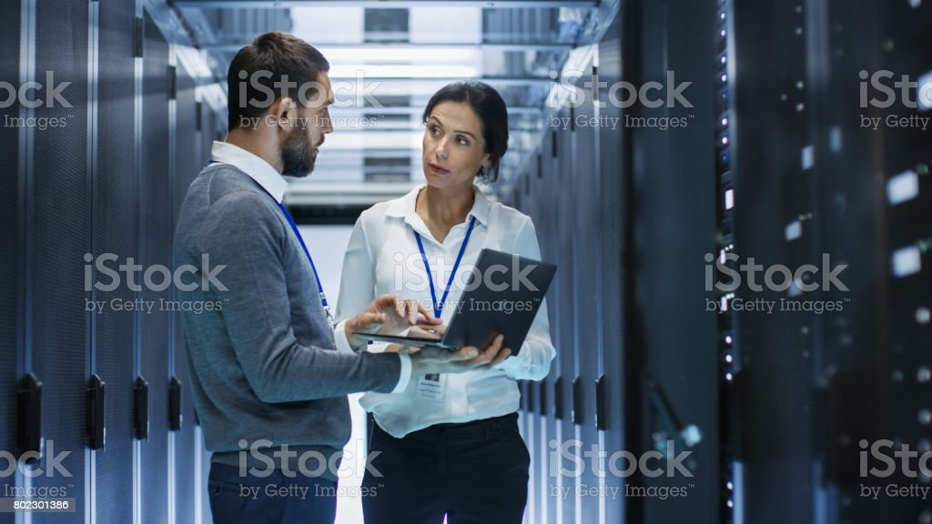 Male IT Specialist Holds Laptop and Discusses Work with Female Server Technician. They're Standing in Data Center, Rack Server Cabinet is Open. royalty-free stock photo