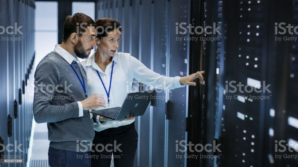 Male IT Specialist Holds Laptop and Discusses Work with Female Server Technician. They're Standing in Data Center, Rack Server Cabinet is Open. - Royalty-free Administrator Stock Photo