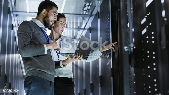 istock Male IT Specialist Holds Laptop and Discusses Work with Female Server Technician. They're Standing in Data Center, Rack Server Cabinet is Open. 802301404