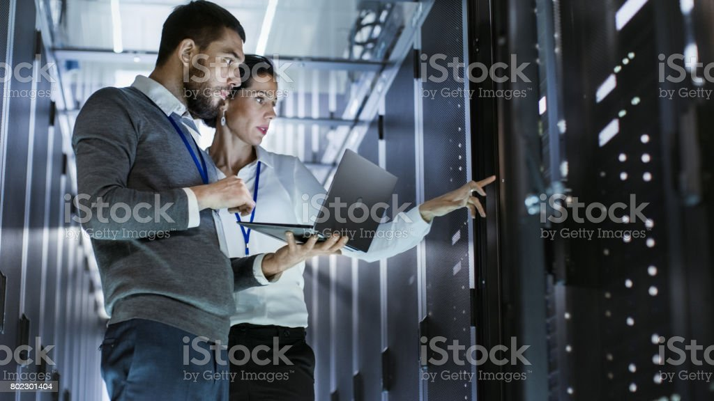 Male IT Specialist Holds Laptop and Discusses Work with Female Server Technician. They're Standing in Data Center, Rack Server Cabinet is Open. stock photo