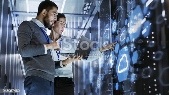 istock Male IT Specialist Holds Laptop and Discusses Work with Female Server Technician. They're Standing in Data Center, Rack Server Cabinet with Cloud Server Icon and Visualization. 943067460