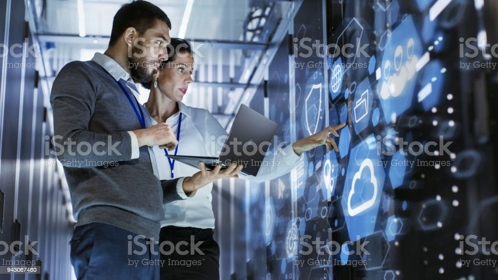Male IT Specialist Holds Laptop and Discusses Work with Female Server Technician. They're Standing in Data Center, Rack Server Cabinet with Cloud Server Icon and Visualization. stock photo