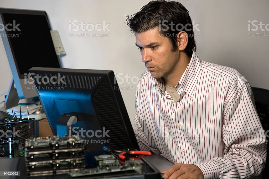 Male IT Technician At Computer Terminal in Office royalty-free stock photo