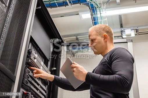istock Male IT Technician Holding Digital Tablet Analyzing Servers in Datacenter 1145071323