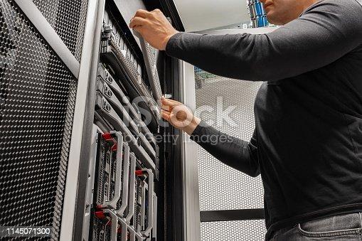 istock Male IT Technician Installing Drive In Rack 1145071300