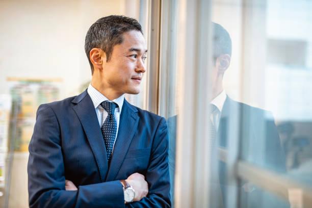 窓に立っている男性日本人病院管理者 - 腕組み スーツ ストックフォトと画像