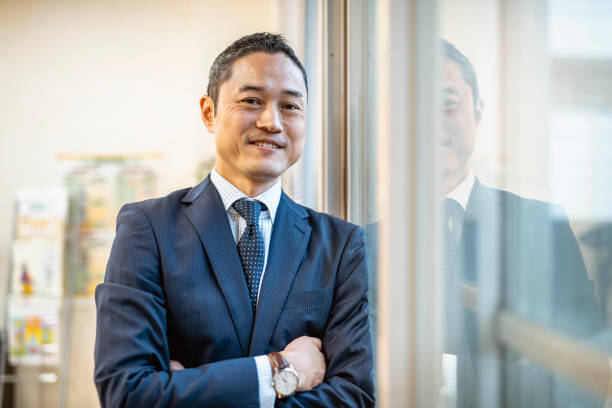 Male Japanese Hospital Administrator Standing at Window Smiling male hospital administrator in a blue suit taking a break from his busy day to look out an office window. administrator stock pictures, royalty-free photos & images