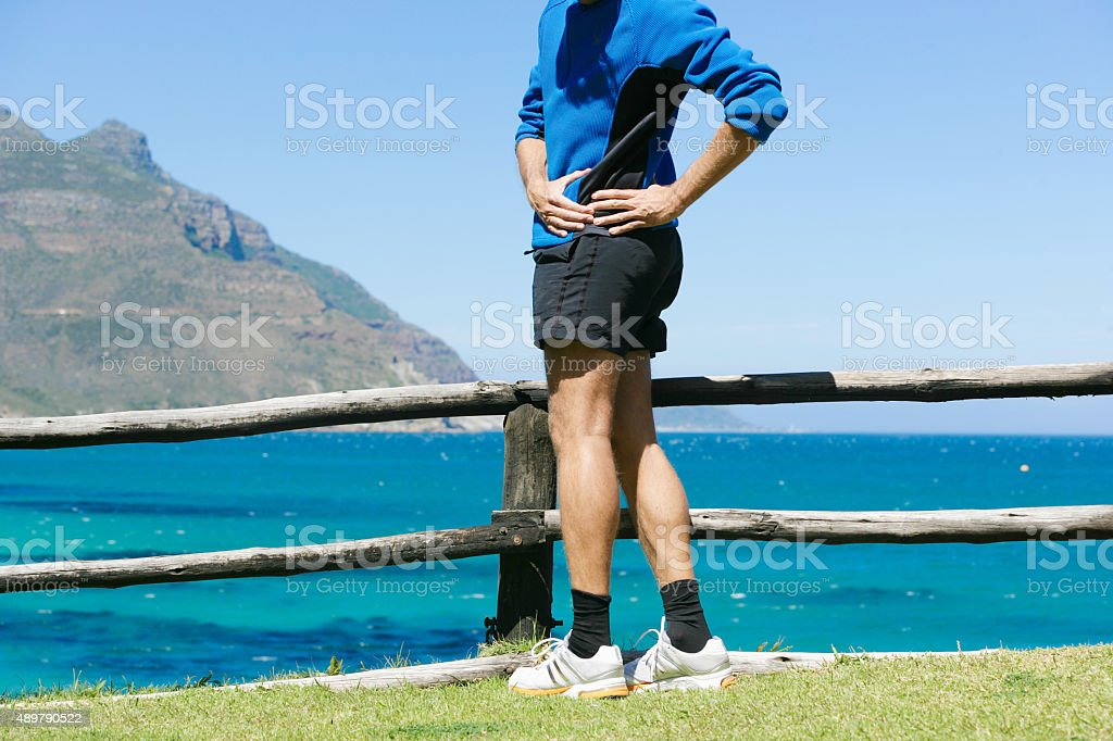 Male jogger hawing lower back pain in Cape Town area stock photo