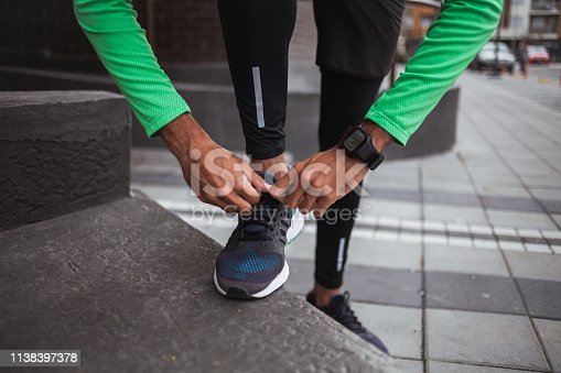 Close up Male jogger tying his shoe