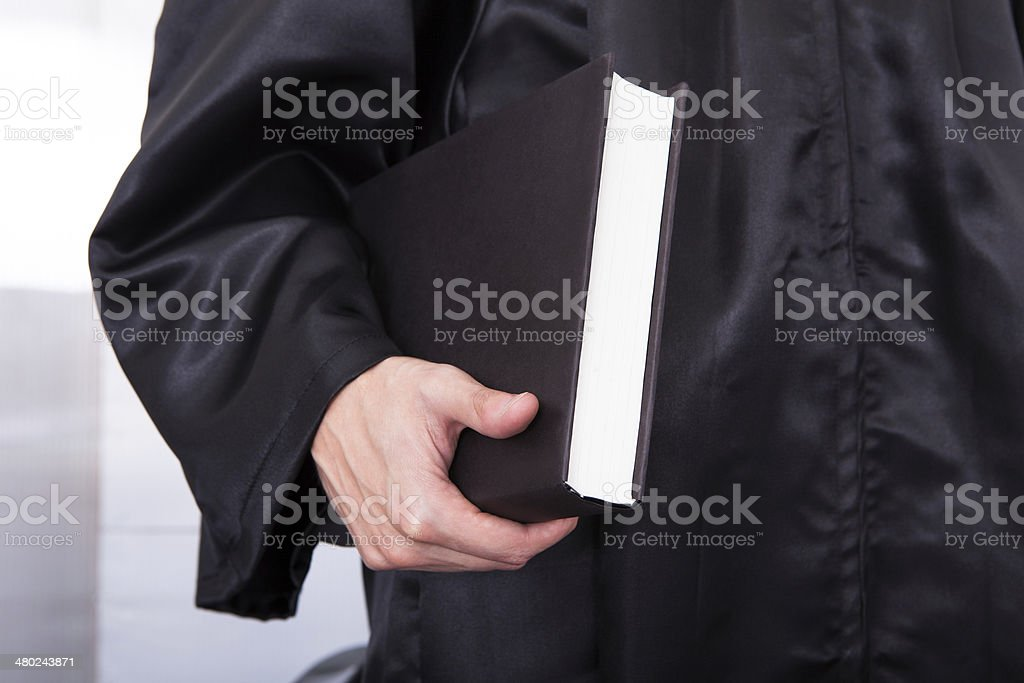 Male Judge Holding Law Book Close-up Of Male Judge In Robe Holding Law Book Adult Stock Photo
