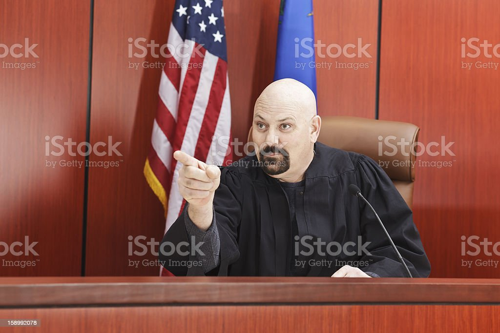 Male Judge Pointing While Seated in Courtroom royalty-free stock photo
