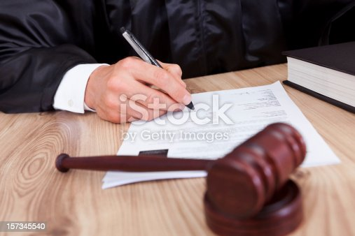 Male Judge Writing On Paper In Courtroom