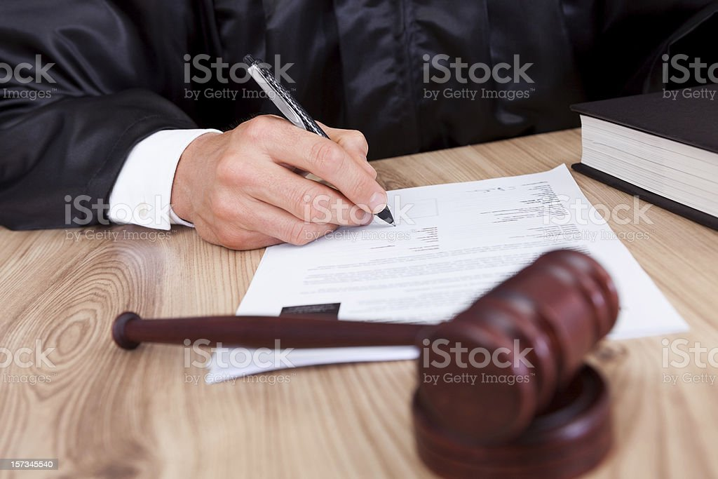 Male judge signing papers with a gavel in front of him stock photo