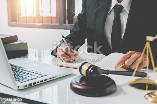 istock Male judge working with contract papers on white wooden table in courtroom. Laptop computer, legal books and gavel on white desk. justice and law concept. 1088618430