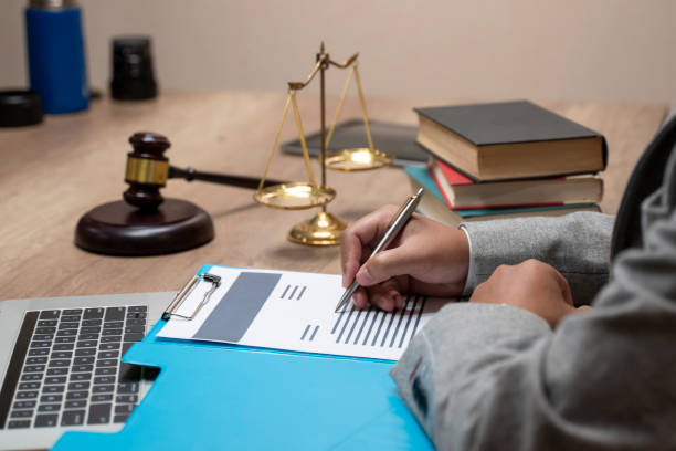 Male judge working with contract papers on white wooden table in courtroom. Laptop computer, legal books and gavel on white desk. justice and law concept. stock photo