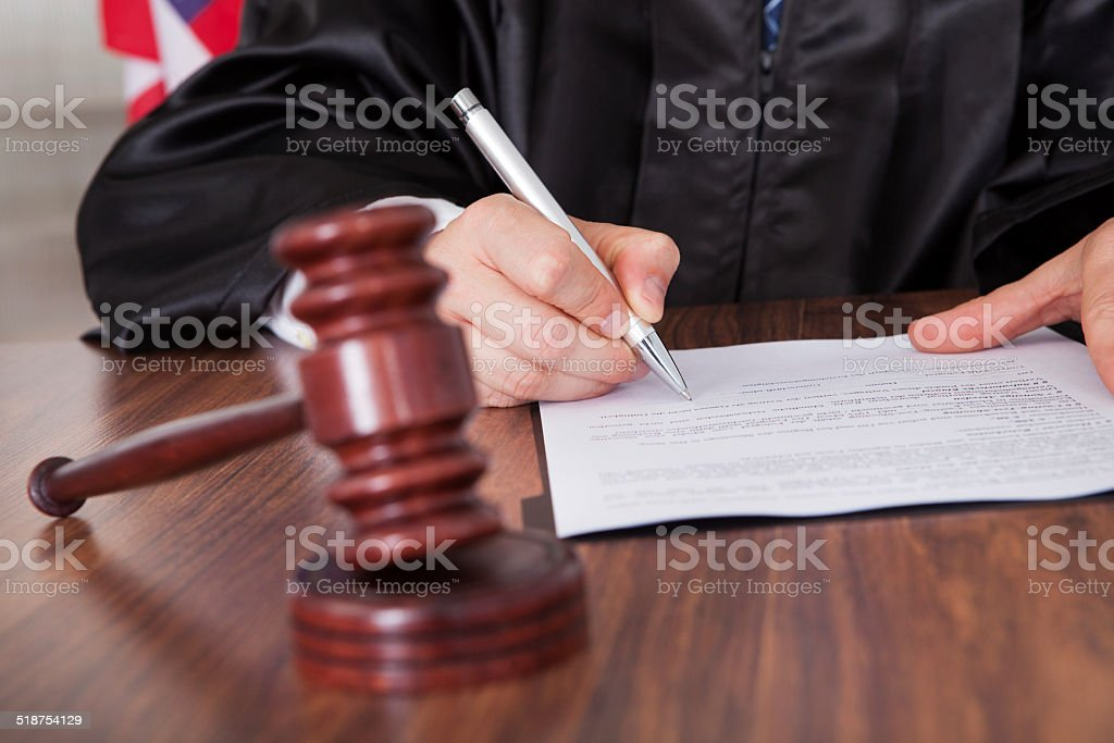 Male Judge Writing On Paper stock photo