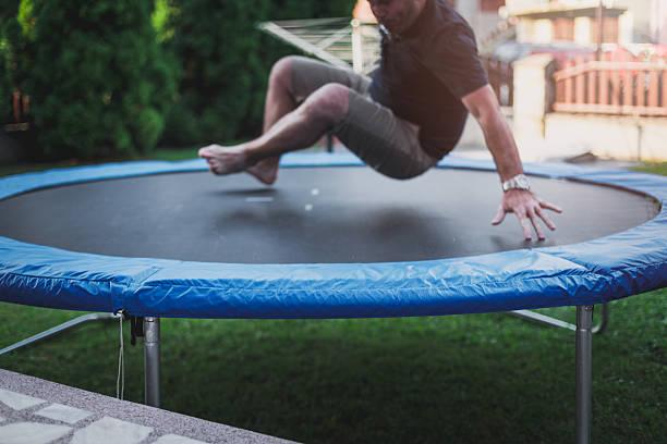 male jumping on a trampoline in the backyard - gartentrampolin stock-fotos und bilder