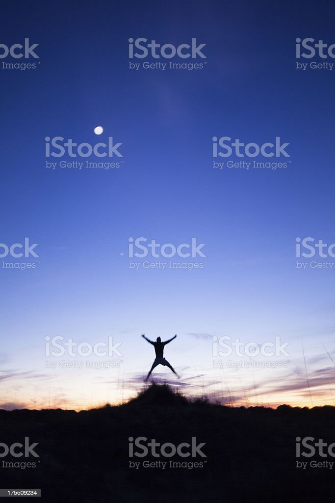 Male jumping with arms outstretched while running at sunset royalty-free stock photo