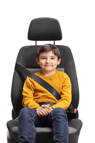 Male kid sitting in a car seat with safety belt on stock photo