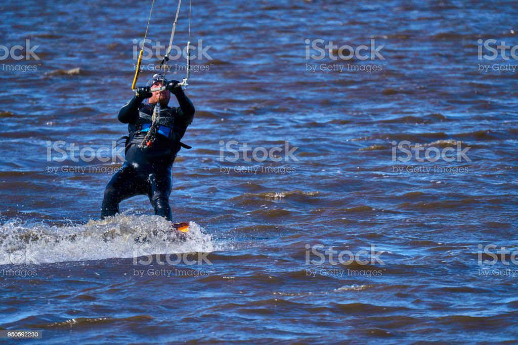 A male kiteboarder rides on a board along the river. He performs various exercises while moving on water. Water still muddy river, the ice has just melted. Sunny spring day. stock photo