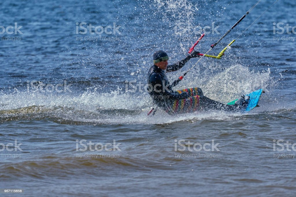 A male kiteboarder rides on a board on a large river. He performs various exercises while moving on water. Splashes of water scatter in different directions. The sun's rays shine in the water. Sunny spring day. stock photo