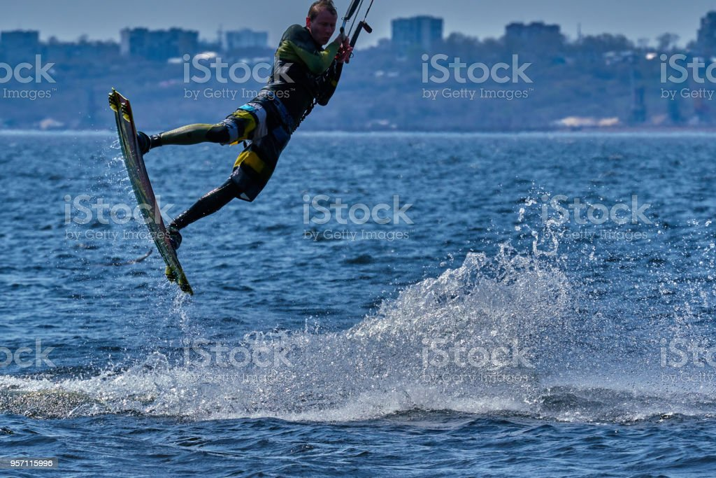 A male kiteboarder rides on a board on a large river. stock photo