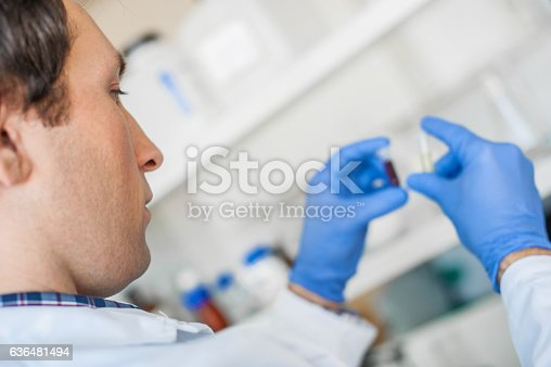 Male lab technician holding a test tube with sample in the medical or scientific laboratory