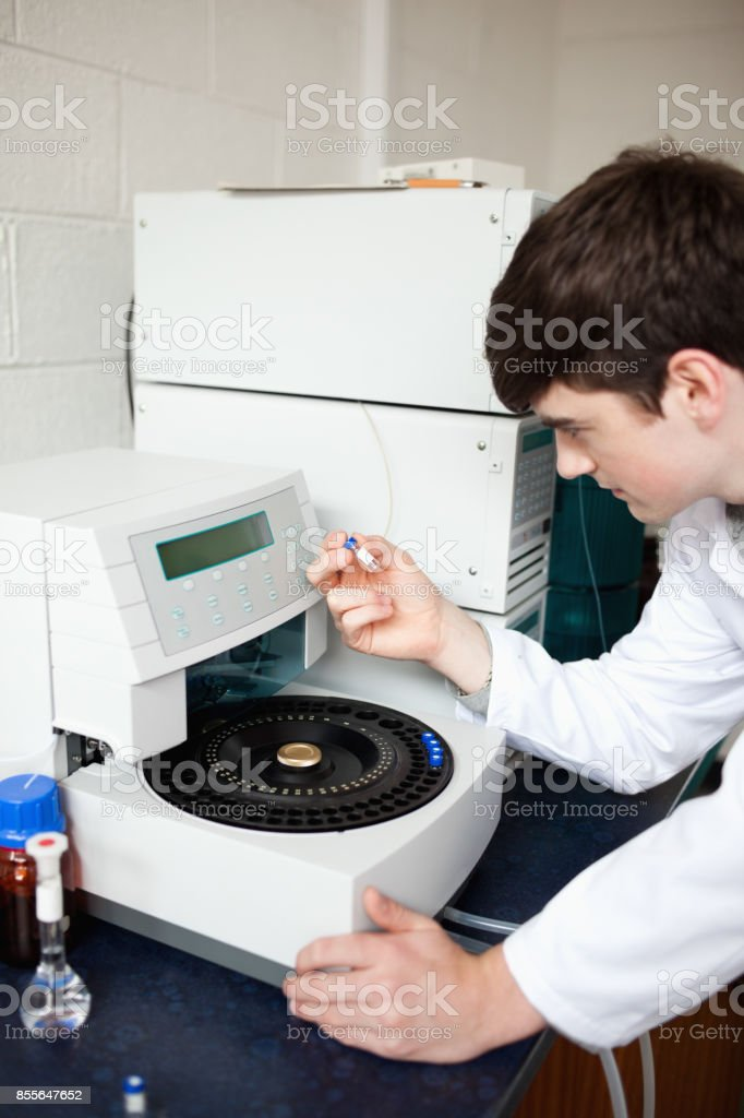 Male laboratory assistant using a centrifuge stock photo