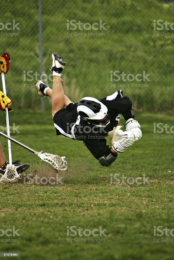 Male Lacrosse Player Flies in Horizontal Dive Capturing Ball royalty-free stock photo