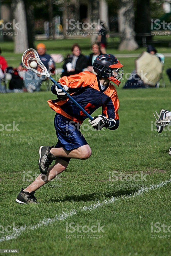 Male Lacrosse Player in Blue Orange Springs to Action Attack royalty-free stock photo