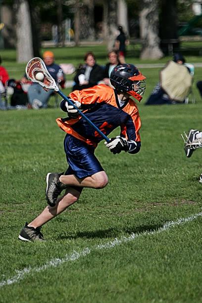mężczyzna lacrosse piłkarz w kolorze niebieskim, pomarańczowym skoki do działania ataku - lacrosse zdjęcia i obrazy z banku zdjęć