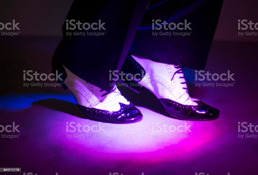 Male latin and salsa dancer in black and white jazz dancing shoes in light and dark on stage stock photo
