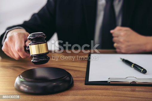 182148217istockphoto Male lawyer or judge hand's striking the gavel on sounding block, working at courtroom for decide home insurance, Law and justice concept, Settle a house dealing lawsuit 885430228