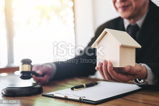 182148217istockphoto Male lawyer or judge hand's striking the gavel on sounding block, working at courtroom for decide home insurance, Law and justice concept, Settle a house dealing lawsuit 931403512