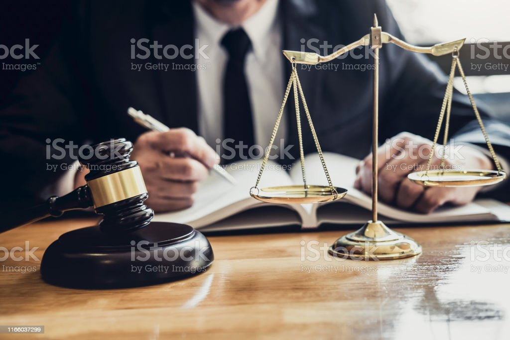 Male Lawyer Or Judge Working With Contract Papers Law Books