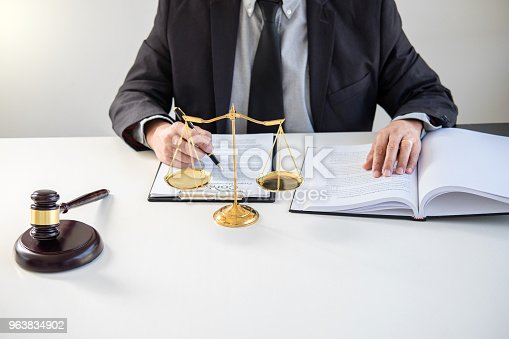 941906652 istock photo Male lawyer or judge working with Law books, gavel, report the case on table in modern office, Law and justice concept 963834902
